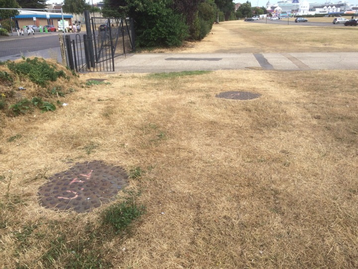 The two manhole covers that forced the access road (behind) to be moved from its original planned location.